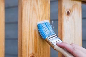човек боядисва дървена ограда с четка